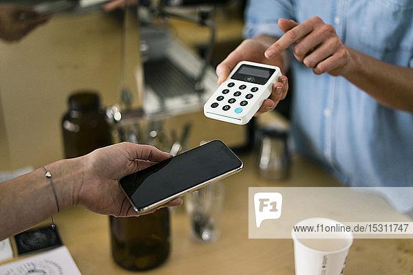 Kunde bezahlt kontaktlos in einem Café
