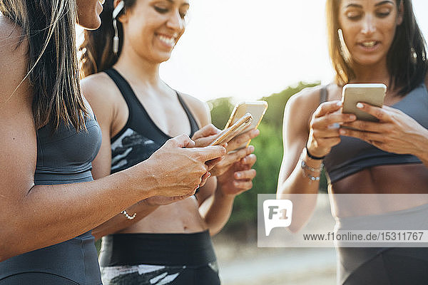 Drei Sportlerinnen benutzen nach dem Training Smartphones