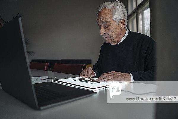 Älterer Mann benutzt Tablett mit Architekturplan