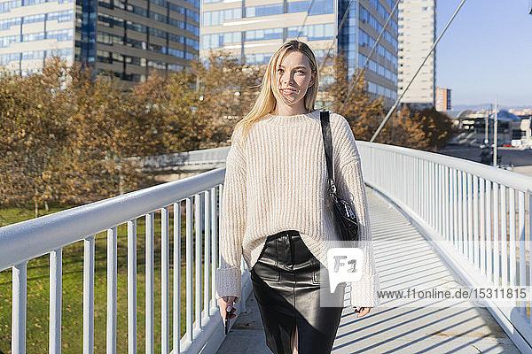 Porträt einer blonden jungen Frau mit Smartphone  die auf einer Fußgängerbrücke geht