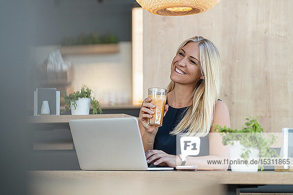 Portrait of smiling blond businesswoman with laptop and glass of orange juice in a coffee shop