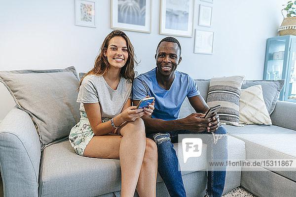 Porträt eines lächelnden Paares im Wohnzimmer mit Mobiltelefonen