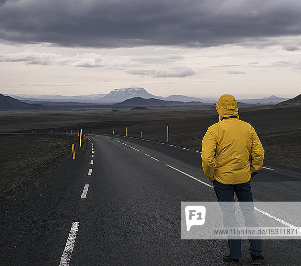 Man standing at empty road  looking at distance  Iceland