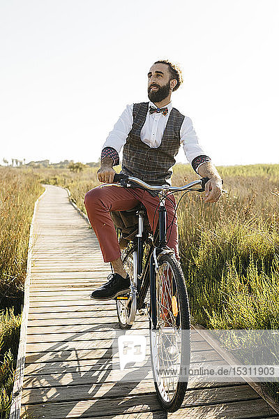 Well dressed man with his bike on a wooden walkway in the countryside having a break