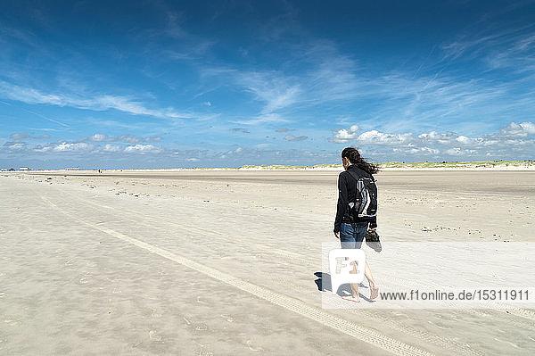 Deutschland  Schleswig-Holstein  Sankt Peter-Ording  Frau  die bei Ebbe am Strand spazieren geht