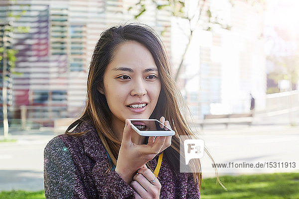 Woman sending a voice message with cell phone  Barcelona  Spain