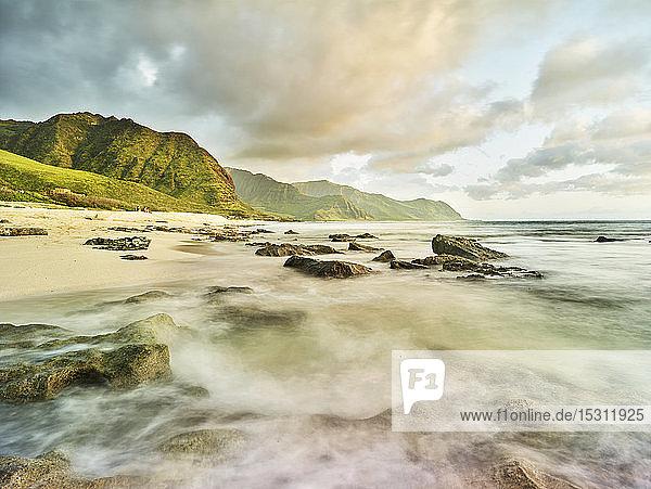 Szenische Ansicht der Wellen  die am Strand am Strand im Ka'ena Point State Park gegen den Himmel plätschern