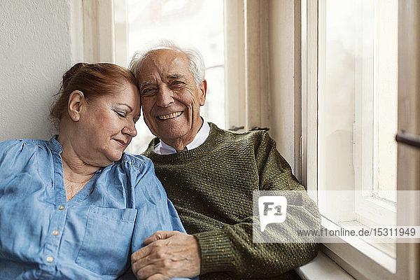Porträt eines glücklichen älteren Ehepaares am Fenster