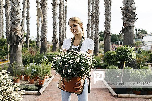 Porträt einer lächelnden Arbeiterin in einem Gartencenter mit einer Gänseblümchenpflanze