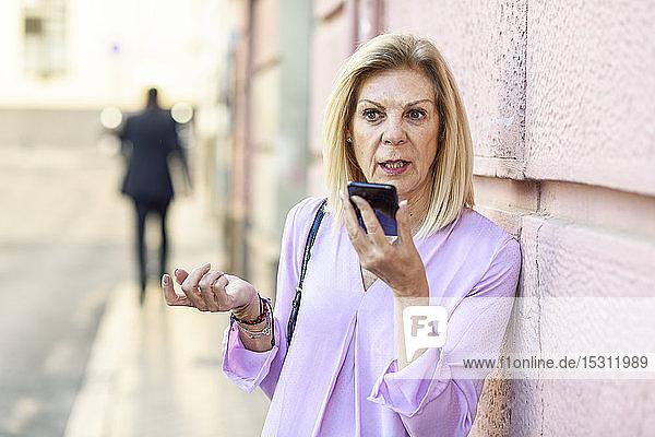 Reife Frau benutzt Smartphone in der Stadt