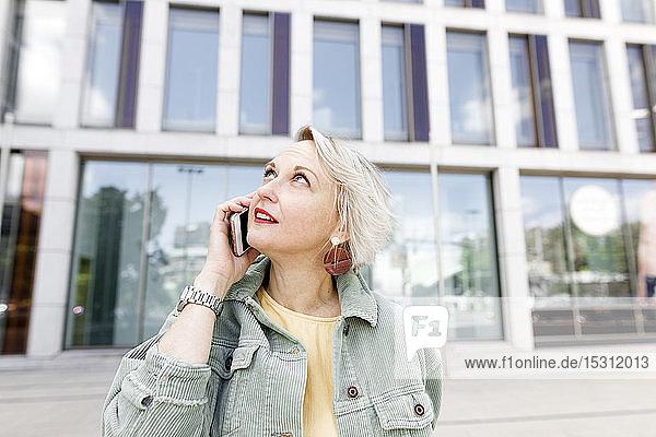 Frau in der Stadt  die draußen steht und ihr Smartphone benutzt