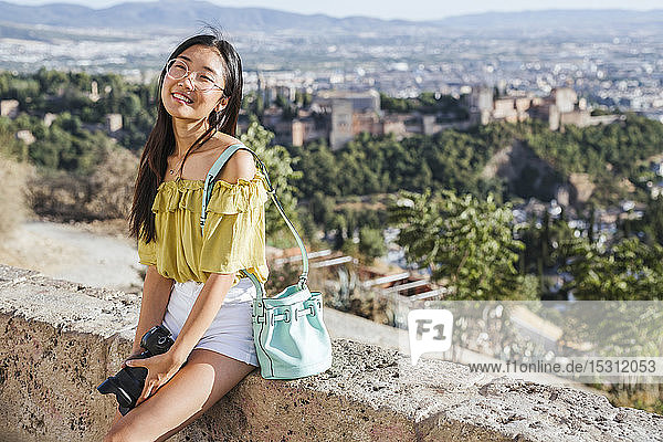 Smiling young woman with camera at the Alhambra  Granada  Spain
