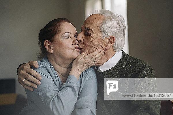Älteres Paar küsst sich zu Hause