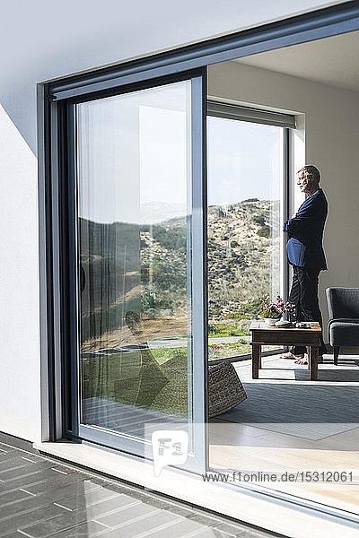 Leitender Geschäftsmann steht am Panoramafenster und schaut hinaus