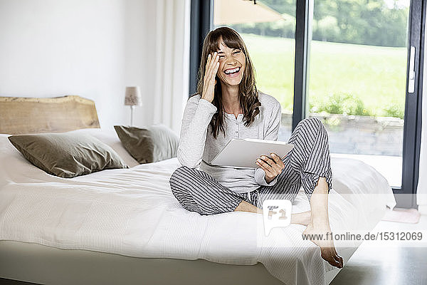 Laughing woman with tablet sitting on bed at home
