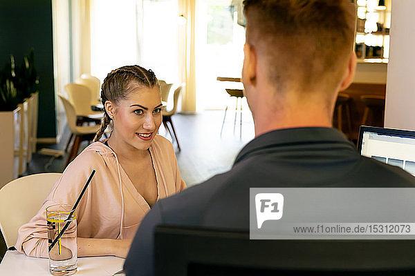 Lächelnde junge Frau betrachtet Mitarbeiterin am Schreibtisch in einem Fitnessstudio