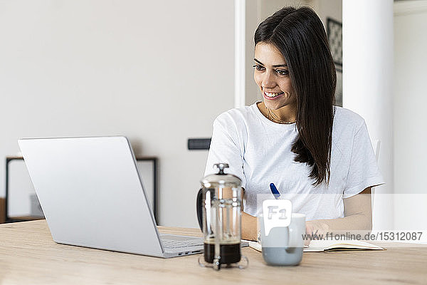 Young woman with laptop taking notes at home