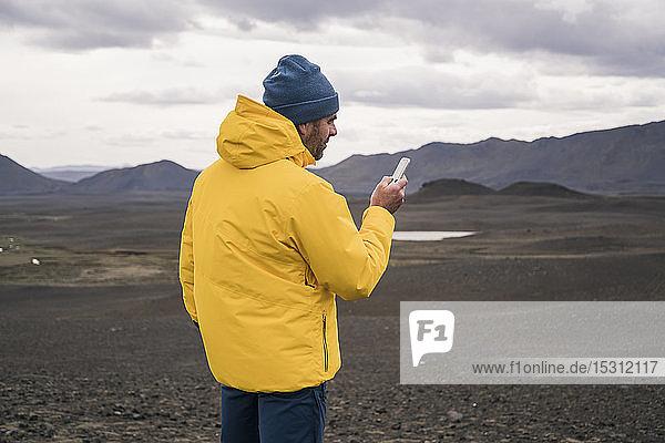 Älterer Mann benutzt Smartphone im isländischen Hochland