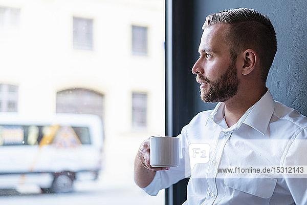 Geschäftsmann im Amt  der eine Kaffeepause macht und aus dem Fenster schaut