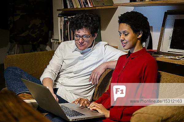 Businessman and businesswoman sitting on couch in office using laptop