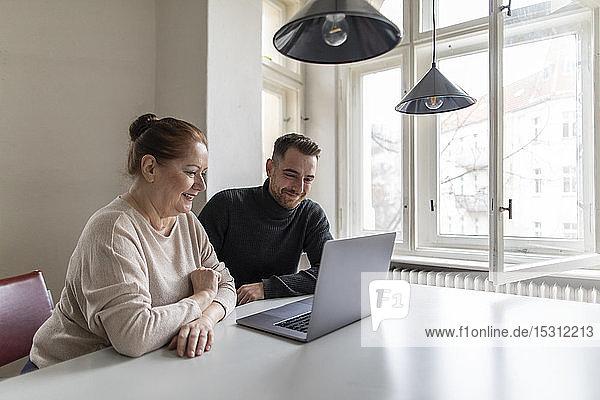 Lächelnde ältere Frau und Mann schauen auf den Laptop auf dem Tisch