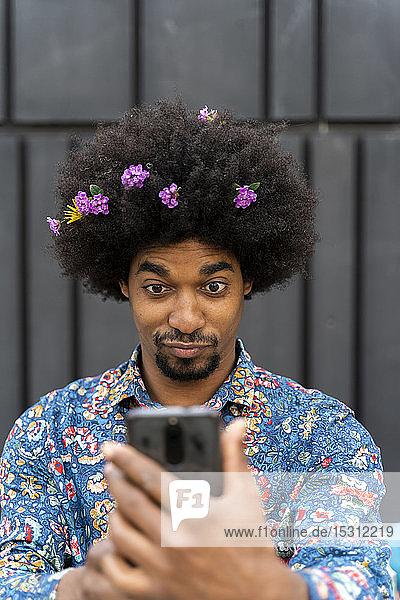 Mann mit Blüten im Haar trägt buntes Hemd und nimmt ein Selfie