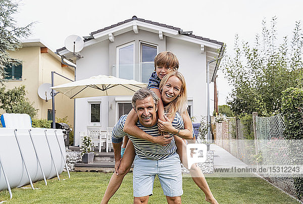 Portrait of father carrying wife and son piggyback in garden
