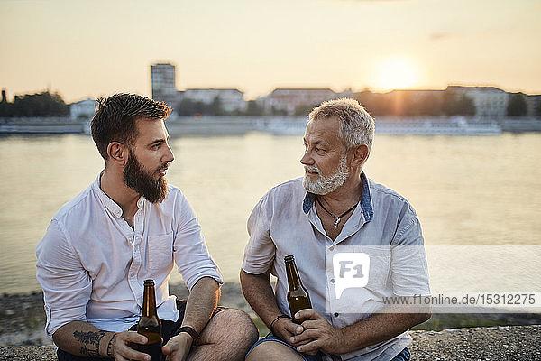 Vater und erwachsener Sohn sitzen bei Sonnenuntergang auf einer Mauer am Flussufer und trinken ein Bier