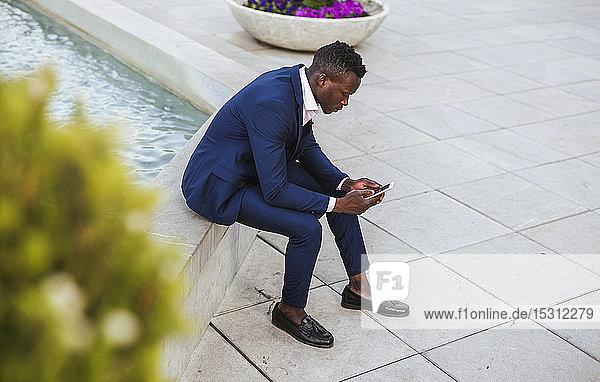 Junger Geschäftsmann benutzt draußen sein Smartphone