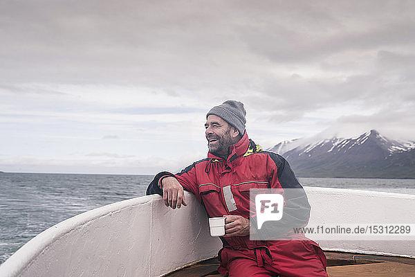 Erwachsener Mann schaut aufs Meer  Bootfahren auf dem Eyjafjordur Fjord  Island