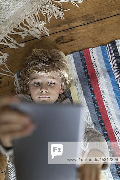 Draufsicht eines auf dem Teppich liegenden Jungen mit Tablette