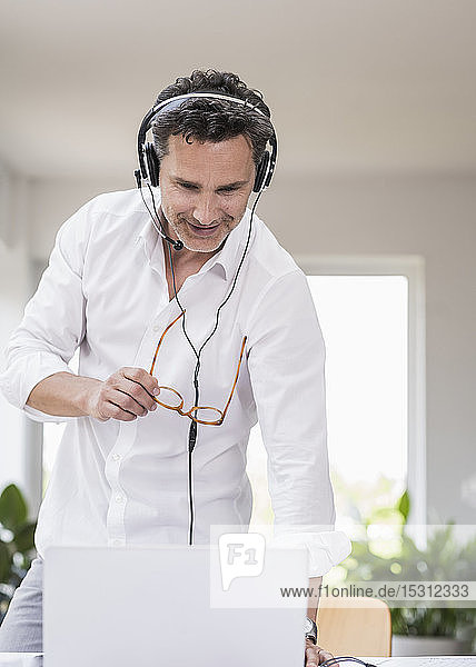 Businessman in bright office having conference call  using headset and laptop