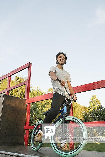 Young man with BMX bike at skatepark having a break