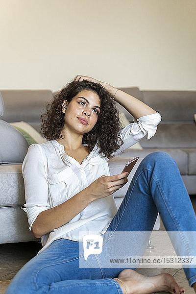Junge Frau sitzt zu Hause mit Handy auf dem Boden