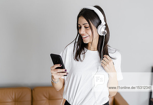 Happy young woman with smartphone and headphones at home