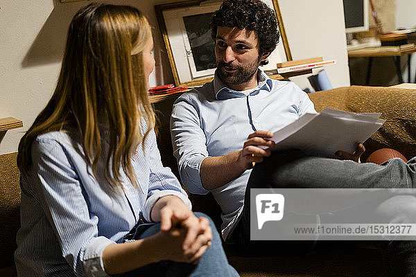 Businessman and businesswoman sitting on couch in office discussing papers