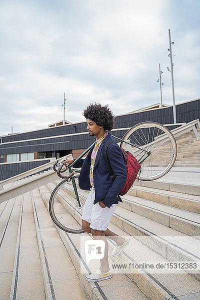 Stilvoller Mann trägt Fahrrad auf Treppen in der Stadt