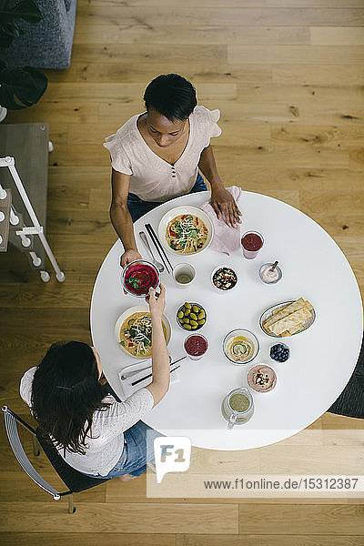 Two women sitting at table having a healthy meal