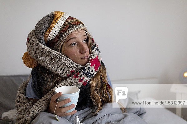 Ill young woman drinking tea in bed at home