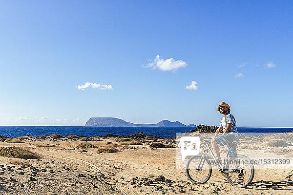 Man on a bicycle  La Graciosa island  Lanzarote  Canary Islands  Spain