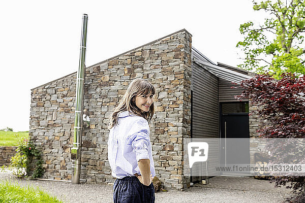Smiling woman standing in front of a house