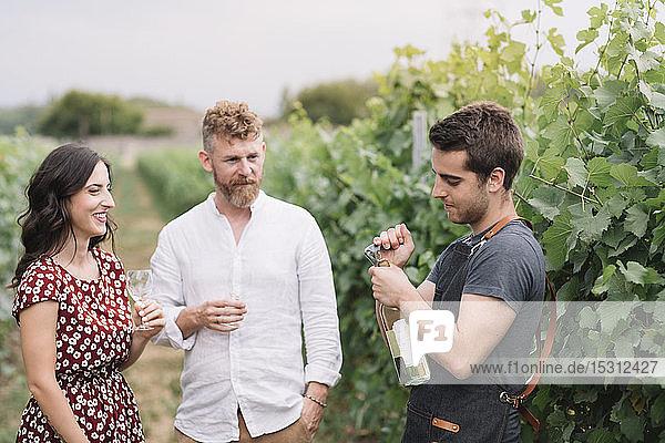 Sommelier öffnet Weinflasche für Kunden im Weinberg