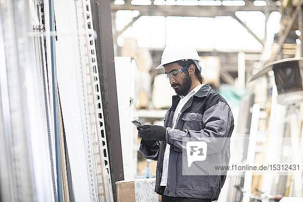 Junger Mann mit Handy und Schutzhelm bei der Arbeit in einem Lagerhaus