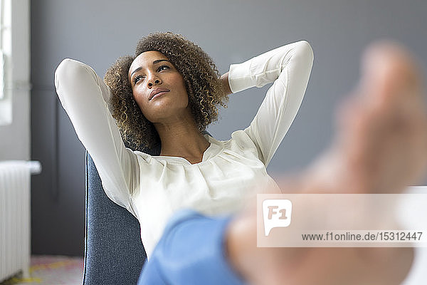 Portrait of young woman relaxing with feet up on desk
