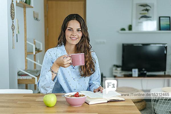 Porträt einer lächelnden jungen Frau beim Frühstück zu Hause