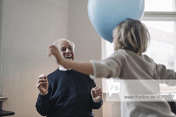 Glücklicher Großvater und Enkel  die zu Hause mit Luftballons spielen