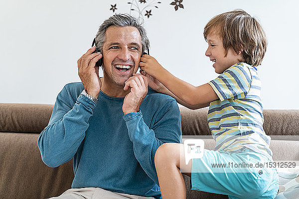 Happy father with boy on couch at home listening to music with headphones