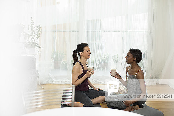 Two relaxed women sitting on gym mat and drinking tea at home