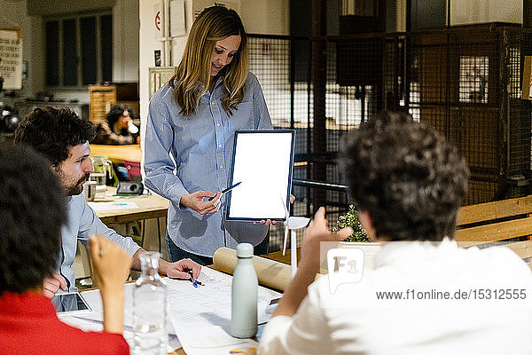 Businesswoman with tablet leading a presentation in office