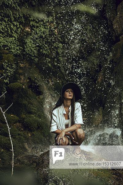 Junge Frau mit Hut  die in der Nähe eines Wasserfalls kauert